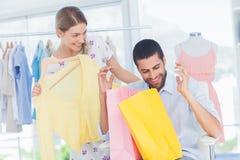 Équipez se reposer dans une boutique tenant des sacs à provisions Photo stock