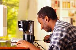 Équipez se reposer par le bureau réparant le petit fabricant de café utilisant le screwdiver, souriant heureusement tout en trava image stock