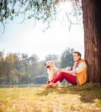 Équipez se reposer par un arbre en parc avec son chien Images stock