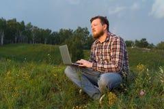 Équipez se reposer sur l'herbe avec un ordinateur portable Image stock