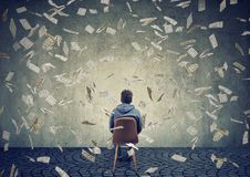 Équipez se reposer sur la chaise devant un mur sous la pluie d'argent Images libres de droits