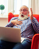 Équipez se reposer sur la chaise rouge et regarder l'ordinateur portable Photo stock
