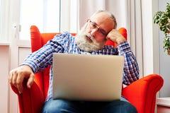 Équipez se reposer sur la chaise rouge et regarder l'ordinateur portable Image stock
