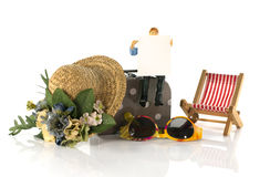 Équipez se reposer sur la valise avec le panneau de destination de voyage Photographie stock libre de droits