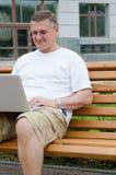 Équipez se reposer sur le banc en bois utilisant un ordinateur portatif photo libre de droits