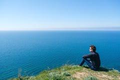 Équipez se reposer sur le bord de la falaise au bord Photo libre de droits