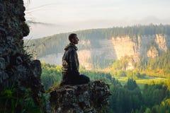 Équipez se reposer sur le dessus de la montagne et rencontrer le lever de soleil Photo stock