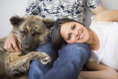 Équipez se reposer sur le plancher avec son chien et amie enceinte Photographie stock libre de droits