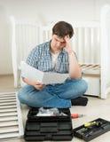 Équipez se reposer sur le plancher et lire le manuel compliqué sur l'assemblin Image stock