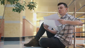 Équipez se reposer sur le plancher, regardant des documents avec des dessins dans le bureau clips vidéos