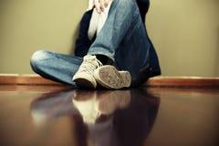 Équipez se reposer sur le plancher se penchant sur le mur Photographie stock libre de droits