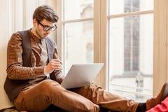 Équipez se reposer sur le rebord de fenêtre et la dactylographie sur l'ordinateur portable photos stock