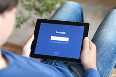 Équipez se reposer sur le sofa et tenir l'iPad avec APP Facebook sur le Th Photo stock