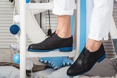 Équipez se reposer sur les jeans blancs de port d'une échelle blanche et les chaussures noires Photo stock
