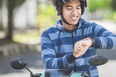 Équipez se reposer sur sa motocyclette et regarder sa montre photo libre de droits