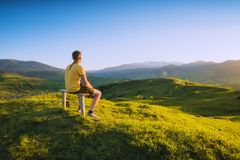 Équipez se reposer sur un banc en bois sur une colline images libres de droits