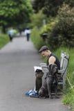 Équipez se reposer sur un banc et lire un livre avec un chien Image stock