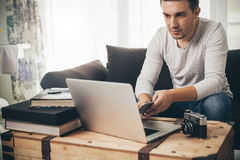 Équipez se reposer sur un sofa travaillant sur l'ordinateur portable Image stock
