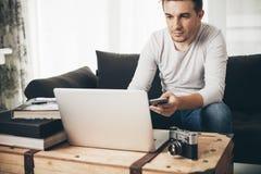 Équipez se reposer sur un sofa travaillant sur l'ordinateur portable Photos stock