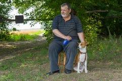 Équipez se reposer sur un tabouret à côté de son chien quadrupède de basenji d'ami en parc d'été Photographie stock