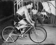 Équipez se reposer sur une bicyclette stationnaire faisant l'exercice (toutes les personnes représentées ne sont pas plus long vi Photographie stock