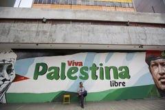 Équipez se reposer sur une chaise et la peinture de Chavez et de Viva Palestina Photographie stock libre de droits