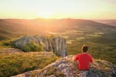 Équipez se reposer sur une colline rocheuse et appréciez le coucher du soleil image libre de droits