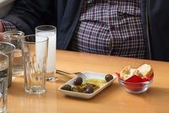 Équipez se reposer sur une table avec des olives et l'ouzo photo libre de droits