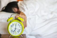 Équipez se situer dans le lit arrêtant un réveil pendant le matin Photographie stock