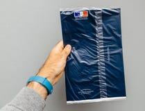Équipez se tenir contre l'enveloppe grise de fond contenant le ` h de Taxe d Photographie stock libre de droits