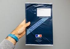 Équipez se tenir contre l'enveloppe grise de fond contenant le ` h de Taxe d Image libre de droits