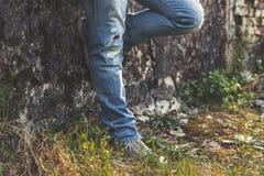 Équipez se tenir prêt le vieux mur, les jeans déchirés par bleu de port et les espadrilles de toile Image libre de droits