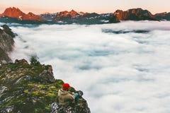 Équipez seule la détente sur des montagnes de bord de falaise au-dessus des nuages image stock