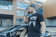 Équipez sortir de la voiture noire et parler par le téléphone portable Vue de côté photo stock