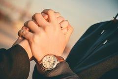 Équipez tenir des mains du ` s de femme avec la bague de fiançailles et faire la proposition dehors Photographie stock