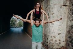 Équipez tenir et élever la femme avec les bras dans une danse de gymnastique Photos libres de droits