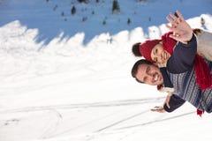 Équipez tenir l'amie sur le sien de retour en haut de la montagne Photo stock