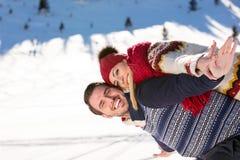 Équipez tenir l'amie sur le sien de retour en haut de la montagne Photos libres de droits