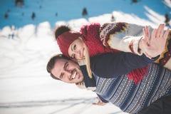 Équipez tenir l'amie sur le sien de retour en haut de la montagne Photo libre de droits