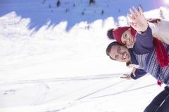 Équipez tenir l'amie sur le sien de retour en haut de la montagne Image stock
