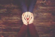 Équipez tenir l'image de vue supérieure de mains du ` s de femme sur le contexte en bois foncé Couples dans le concept d'amour Image stock
