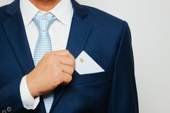Équipez tenir tenir la carte de crédit en blanc sur le fond gris Images stock