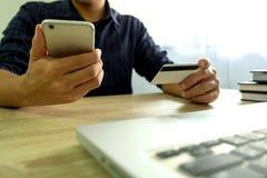 Équipez tenir la carte de crédit et à l'aide du smartphone pour des achats de paiement photos libres de droits