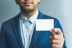 Équipez tenir la carte de visite professionnelle de visite blanche, homme utilisant la chemise bleue et montrant la carte de visi Image stock