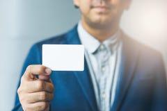 Équipez tenir la carte de visite professionnelle de visite blanche, homme utilisant la chemise bleue et montrant la carte de visi Photo libre de droits