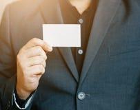 Équipez tenir la carte de visite professionnelle de visite blanche, homme utilisant la chemise bleue et montrant la carte de visi Photos stock