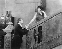 Équipez tenir la main d'une femme se tenant sur un escalier (toutes les personnes représentées ne sont pas plus long vivantes et  Photographie stock libre de droits