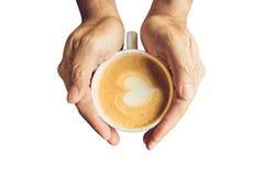 Équipez tenir la tasse chaude de forme de café et de coeur Image stock