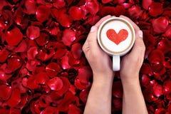 Équipez tenir la tasse chaude de lait sur le fond rouge de pétales de rose, avec la forme rouge de coeur Photos libres de droits