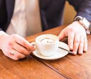 Équipez tenir la tasse de café sur le fond en bois photos stock